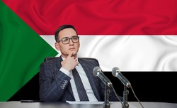 Young man in glasses and a jacket at an international meeting or press conference negotiations, on the background of the flag suriname