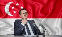 Young man in glasses and a jacket at an international meeting or press conference negotiations, on the background of the flag Singapore, Singaporean
