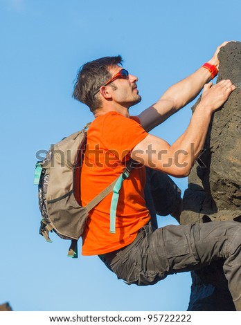 Young man in glasses with backpack climbing outdoor wall.