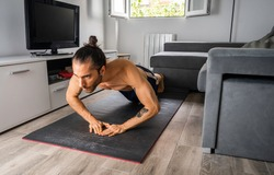 Young man in good physical shape, with bow tie, shirtless, and shorts, doing diamond-style push-ups on a mat on the floor in his bachelor's room, training