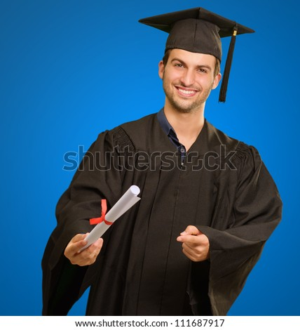 Young Man In Graduation Gown Holding Certificate On Blue Background - stock photo