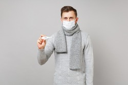 Young man in gray sweater, scarf with sterile face mask holding thermometer isolated on grey background in studio. Healthy lifestyle ill sick disease treatment cold season concept. Mock up copy space