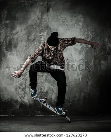 Young man in hat and shirt performing stunt on skateboard 129623273