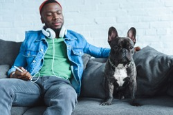 Young man in headphones holding smartphone and sitting by French bulldog