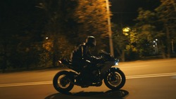 Young man in helmet riding fast on modern sport motorbike at evening city street. Motorcyclist racing his motorcycle on night empty road. Guy driving bike. Concept of freedom and hobby. Side view.