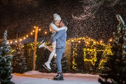 Young man in jeans clothes holding pretty young blond woman in winter white hat and sweater on the ice rink. Snow background.