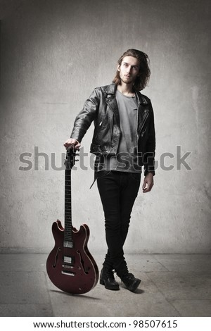 Young man in leather jacket holding a guitar