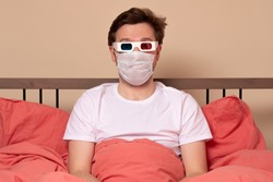Young man in medical mask in 3d glasses watching TV at home in the bed. Stay at home during quarantine