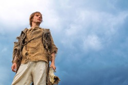 young man in medieval peasant costume on sky background
