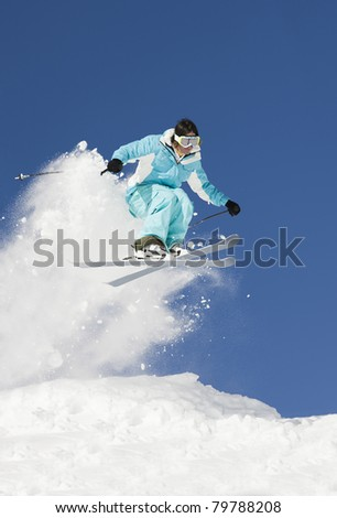 Young man in mid-air making jump against blue sky.