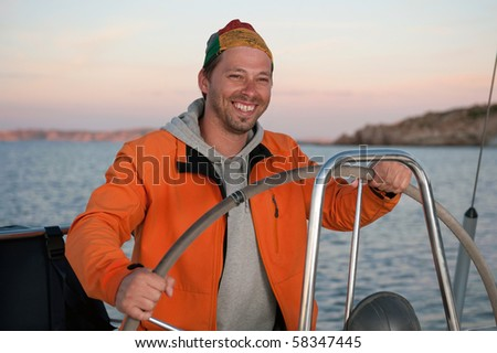young man in orange jacket holding the steering wheel on the yacht during vacation