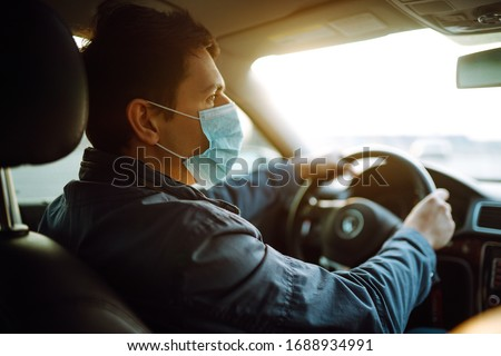 Young man in protective sterile medical mask driving car. The concept of preventing the spread of the epidemic and treating coronavirus, pandemic in quarantine city. Covid -19.
