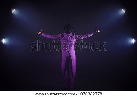 Young man in purple suit standing on the background of the spotlight. Showman spreading hands, show begins. Back view #1070362778