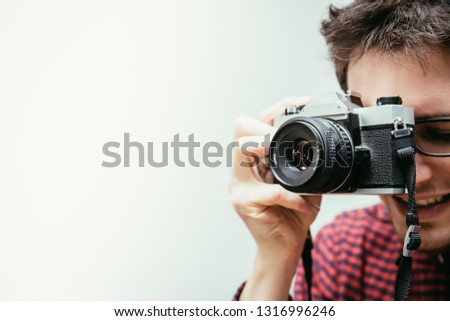 Young man in red-blue checked shirt is taking a picture with an vintage camera, retro style