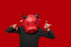 Young man in red mask of a bull cow on the head on an isolated background. Person shows with gestures that he gores. Blank for banner, template, place for advertising text. Businessman. Copy space