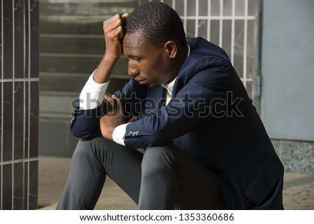 young man in sad depressed sitting suit crying devastated feeling hurt suffering from depression. Depression in people, sadness, emotional pain and loneliness.
