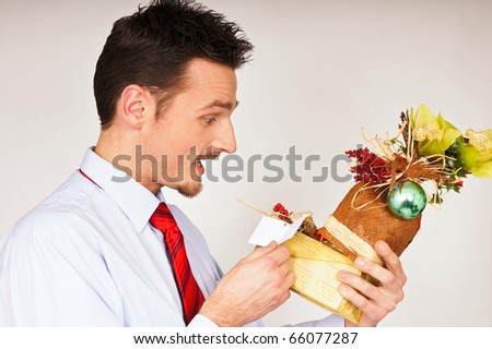 Young man in shirt and red tie hold Christmas gift and he is surprised