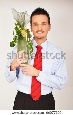 Young man in shirt and tie hold and shows gift.