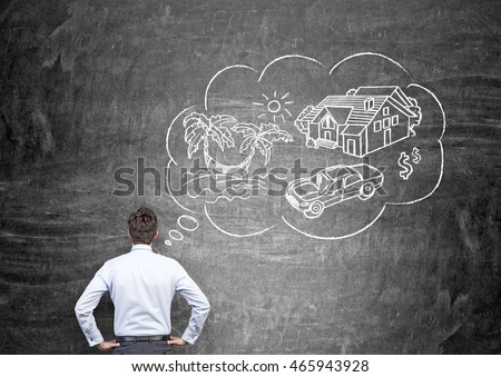 Young man in shirt and trousers is standing with back to viewer in front of blackboard with sketch of travel and car pictured on it. Concept of making dream come true.