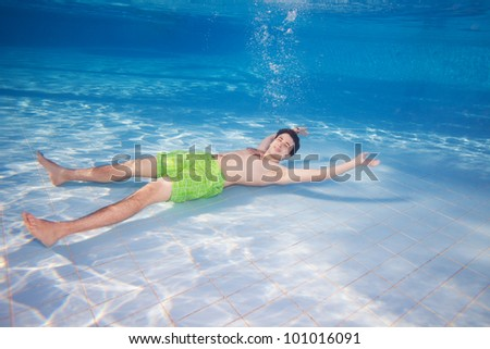 Young man in shirts resting laying underwater on the pool bottom