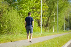 Young man in shorts and t-shirt slowly walking on long sidewalk at town green park. Warm, sunny spring day. Spending time alone in nature. Peaceful atmosphere. Back view.