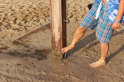 Young man in shorts removing sand form his legs under beach shower near sandy ground, water drops spraying over feet