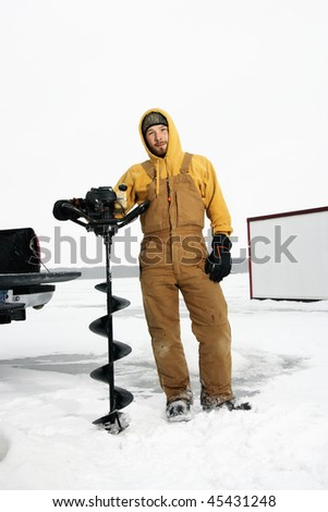 Young man in snow gear poses with an ice drill in a winter environment. Vertical shot.