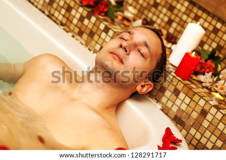 Young man in spa. Romantic jacuzzi with flowers and candles