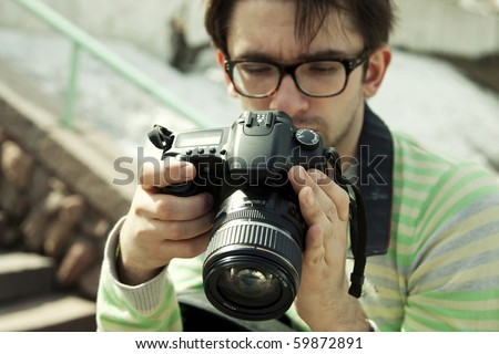 young man in spectacles with a camera