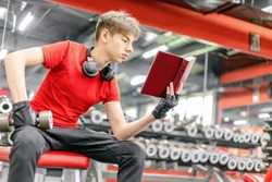 young man in sports clothes and headphones is engaged with dumbbells in the gym learns knowledge by reading a book, develops the body's immune system through training, knowledge is power