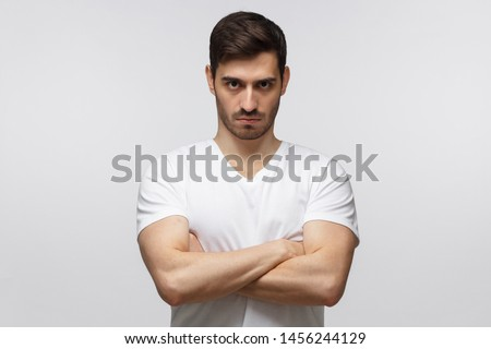 Young man in standing with arms crossed and serious concentrated face at camera, looking aggressive, isolated on gray background