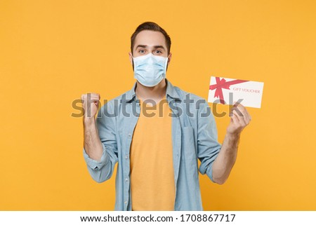 Young man in sterile face mask posing isolated on yellow background studio portrait. Epidemic pandemic coronavirus 2019-ncov sars covid-19 flu virus concept Hold gift certificate doing winner gesture