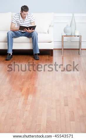Young man in striped shirt and blue jeans sitting on white sofa reading a book. Vertical shot.