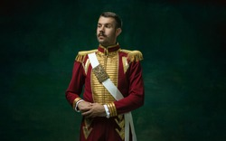 Young man in suit as Nicholas II isolated on dark green background. Retro style, comparison of eras concept. Beautiful male model like historical character, monarch, old-fashioned.