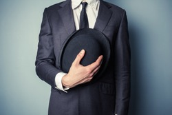 Young man in suit is holding a bowler hat