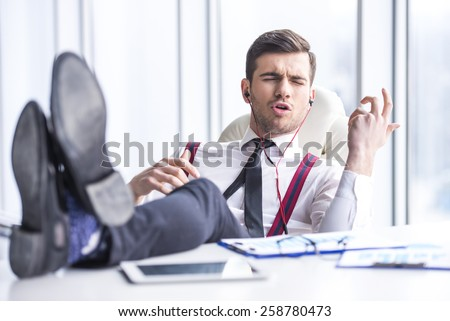 Young man in suit is listening music in headphone in office.