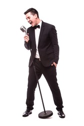 Young man in suit singing over the microphone with energy. Isolated on white background. Singer concept.