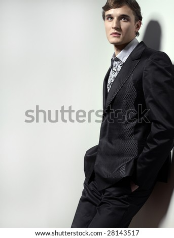 young man in suit standing near the wall