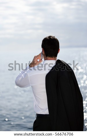 Young man in suit with a phone face to the sea