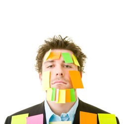 Young man in suit with lots of adhesive notes on his face and body