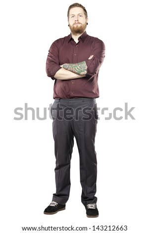 Young man in suit with tattoos against white background looking tough