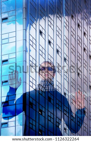 Young man in sunglasses raising hands behind bars of skyscraper glass wall. Conceptual photo on modern architecture, innovative technology, transparent business, urban lifestyle, mission or freedom.