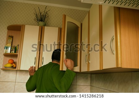 Young man in sweater peeks into kitchen cupboard at home, viewed from the back side. alone hungry man search food.