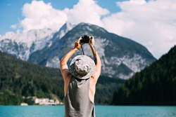 Young man in tan top and panama hat makes photos with digital mirrorless camera of alpine lake with blue water and mountains, nomad explorer, hipster millennial