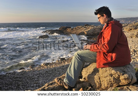 Young man in the beach with laptop