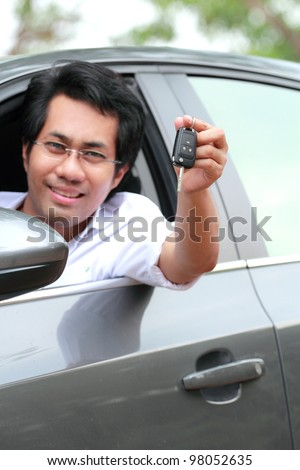 Young man in the car show the key
