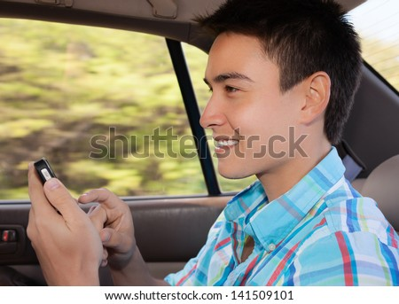Young man in the car using his mobile phone