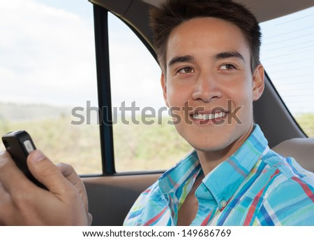 Young man in the car using mobile phone