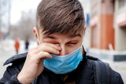Young Man in the Flu Mask on the City Street rub his Eye