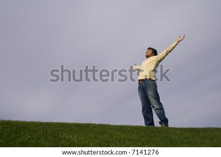 young man in the grass looking to the sky with his arms outstretched